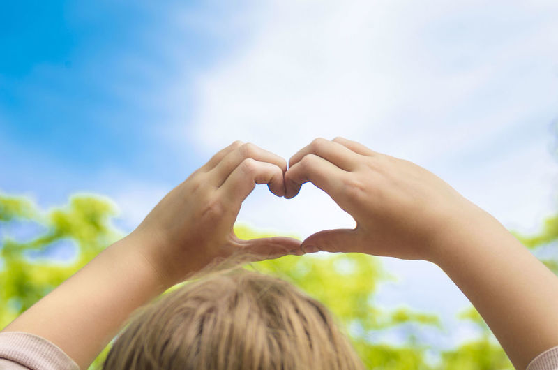 Close-up of child making heart shape against sky