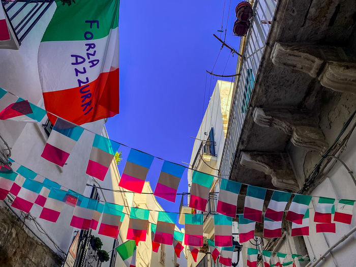 Low angle view of flags hanging against building