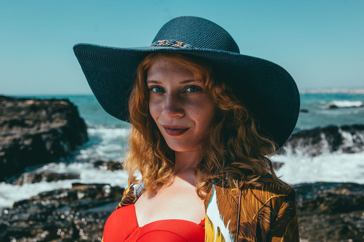 Portrait of young woman in hat against sea