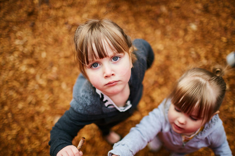 High angle view of siblings standing at park during autumn