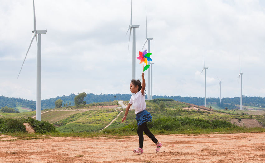 Full length of girl playing with pinwheel toy on land with windmills in background