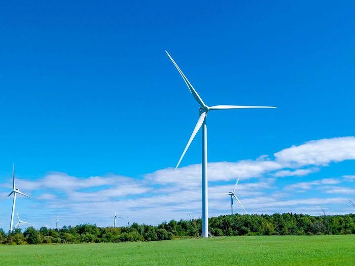 Windmill on field against blue sky