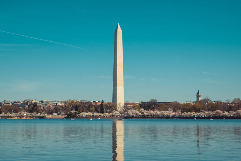 Washington Monument By River Against Sky In City