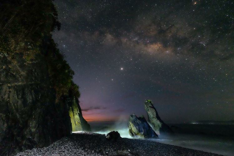 Scenic view of land against sky at night