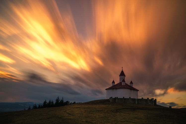 Chapel on hill against sky during sunset