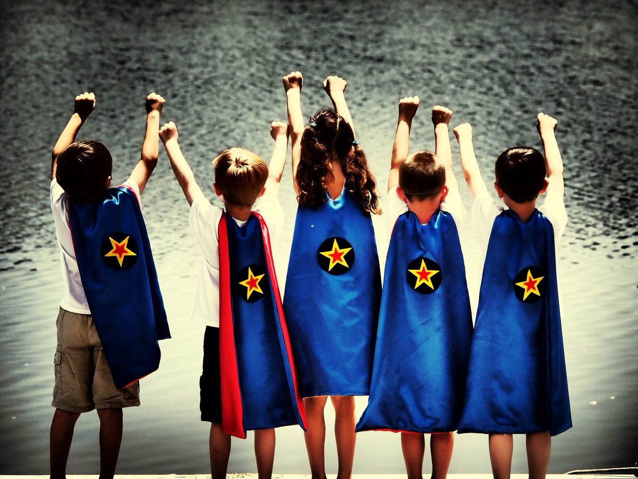 Rear view of children in superhero costume against lake