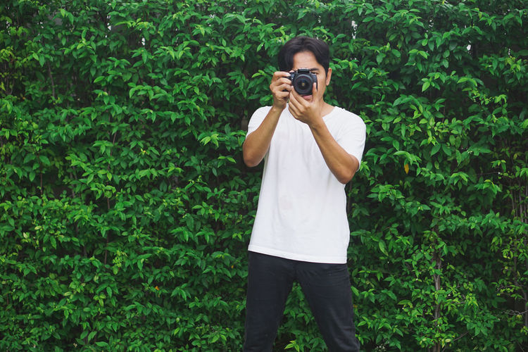Young man photographing on camera