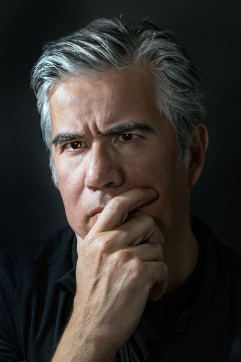 Portrait Headshot One Person Studio Shot Black Background Adult Mature Adult Hand On Chin Indoors  Looking At Camera Gray Hair Men Close-up Mature Men Serious Males  Front View Contemplation Baby Boomer Hairstyle Depression - Sadness