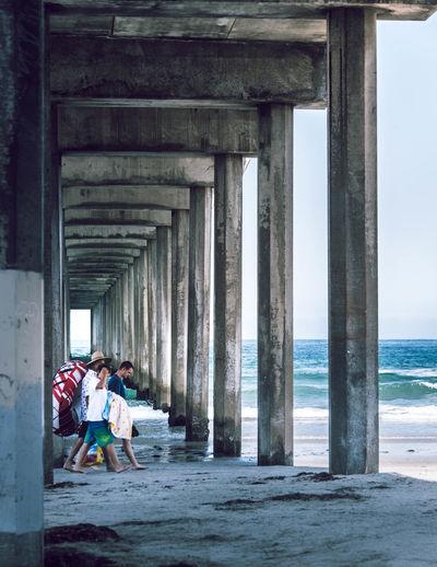 People at beach by bridge