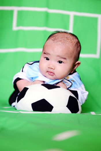 Baby with toy soccer ball on green fabric