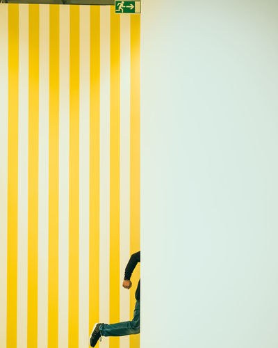 Low section of man against yellow striped wall