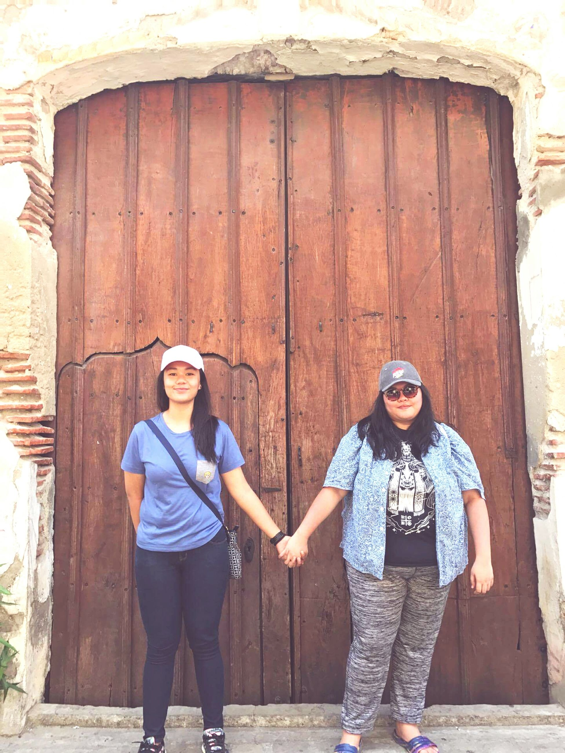 looking at camera, portrait, two people, standing, day, wood - material, door, front view, real people, young women, smiling, young adult, outdoors, togetherness, leisure activity, lifestyles, built structure, architecture, friendship, building exterior