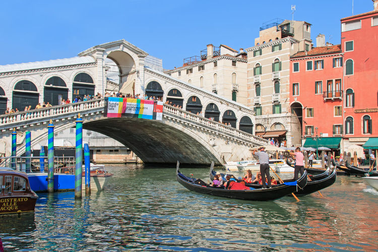 Venice, Italy - June 28, 2014: Gondolas and small boats on the Grand Canal in Venice, Italy, close to Rialto bridge. Some tourists admiring the stunning view. Arch Architecture Bridge - Man Made Structure Building Exterior Canal Grande City Cultures Gondola Gondola - Traditional Boat Gondolier Horizontal Italy Nautical Vessel Outdoors Passenger Craft People Ponte Di Rialto Rialto Saint Mark's Square Tourism Transportation Travel Travel Destinations Vacations Venezia