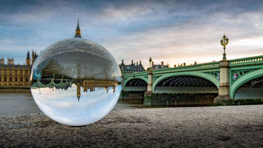 Reflection Of Big Ben And Westminster Bridge On Crystal Ball At Retaining Wall Against Cloudy Sky During Sunset