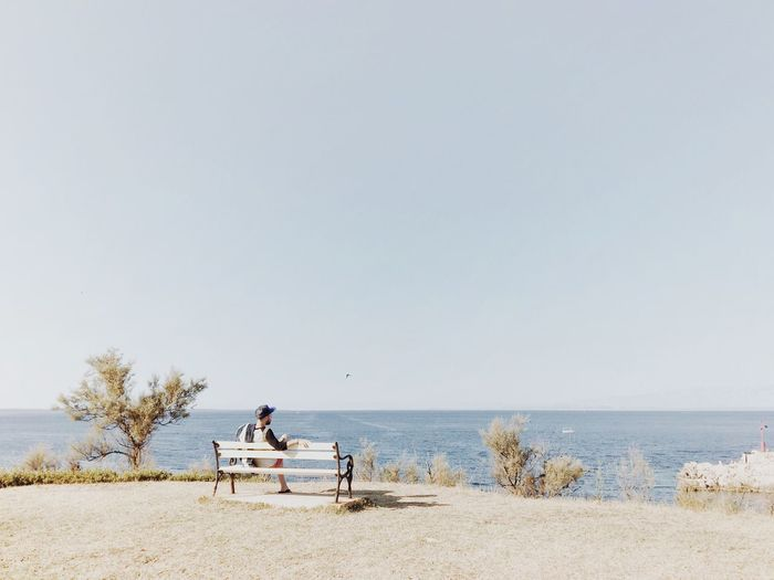 Rear view of man sitting on bench by sea against clear sky