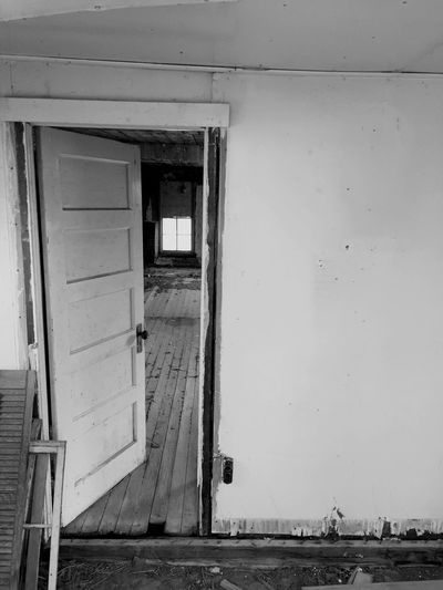 """From Here, To There, A Lifetime"" Peering through this partially open door of an abandoned railroad employee house, across the weathered and worn wood floor to the window, I hauntingly was aware of the lives that once crossed the span and filled the room with living. Abandoned Abandoned Places Abandoned House Haunting  Weathered Blackandwhite Photography Newmexico Rural Decay"