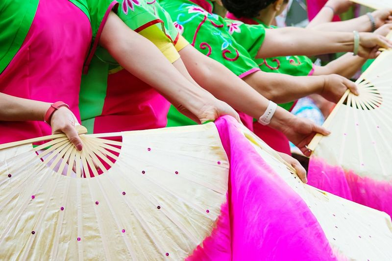 Women In Traditional Costume While Dancing With Folding Fans At Parade