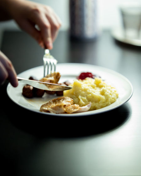 Cropped image of person holding food in plate