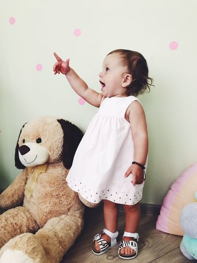 Cute Baby Girl Pointing While Standing By Stuffed Teddy Bear Against Wall