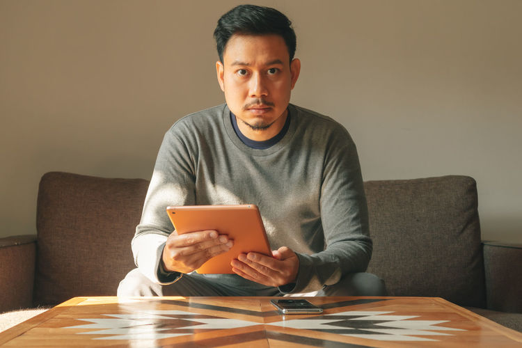 Portrait of man using mobile phone while sitting on sofa at home