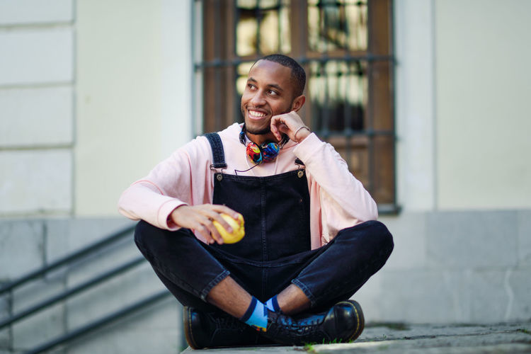 Smiling Young Man Holding Apple While Sitting Outdoors