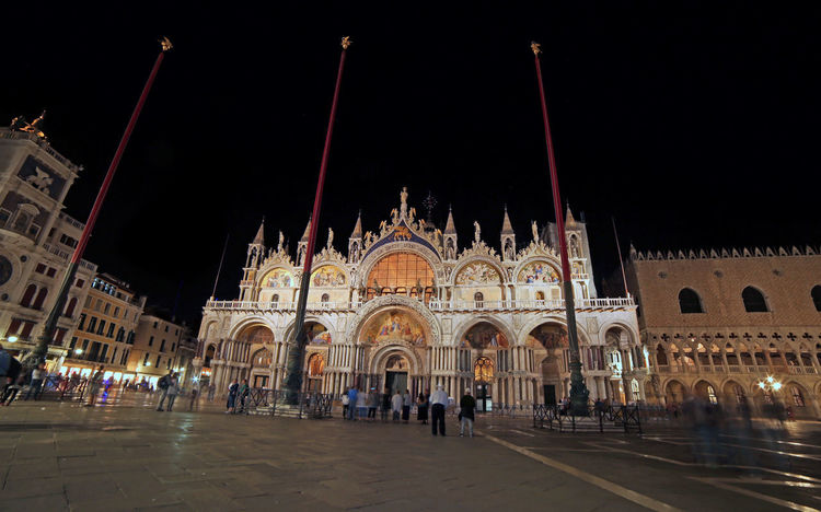 Illuminated Saint Mark Basilica with black sky at night with long exposure in Venice Italy Basilica Saint Mark's  Saint Mark's Basilica Saint Mark's Square Square Venezia Arch Architecture Building Exterior City Crowd Façade Gothic Style Group Of People History Illuminated Italian Night People Religion Saint Mark San Marco Travel Travel Destinations Venice