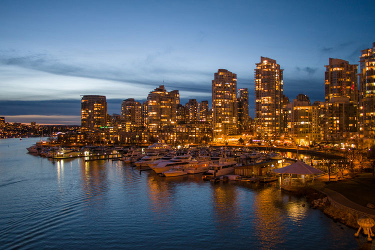 Boats moored at harbor by illuminated cityscape against sky during dusk