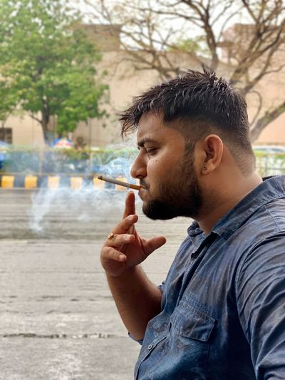 Smoker Cigarette  One Person Smoking Issues Smoking - Activity Bad Habit Lifestyles Young Adult Real People Side View Tobacco Product Smoke - Physical Structure Young Men Activity Casual Clothing Men Outdoors