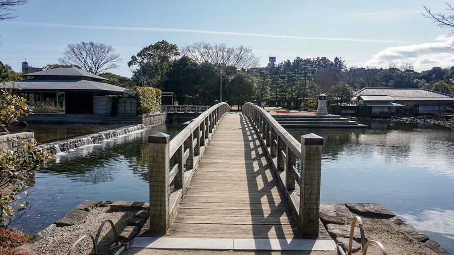 Footbridge over river against sky