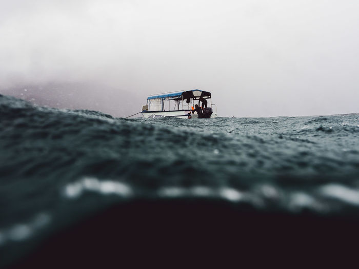 Surface level of boat in sea against sky