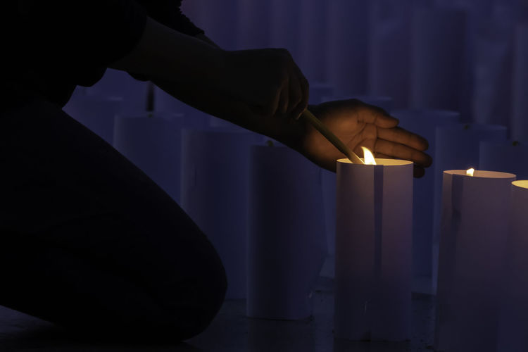 Midsection of person holding illuminated candles