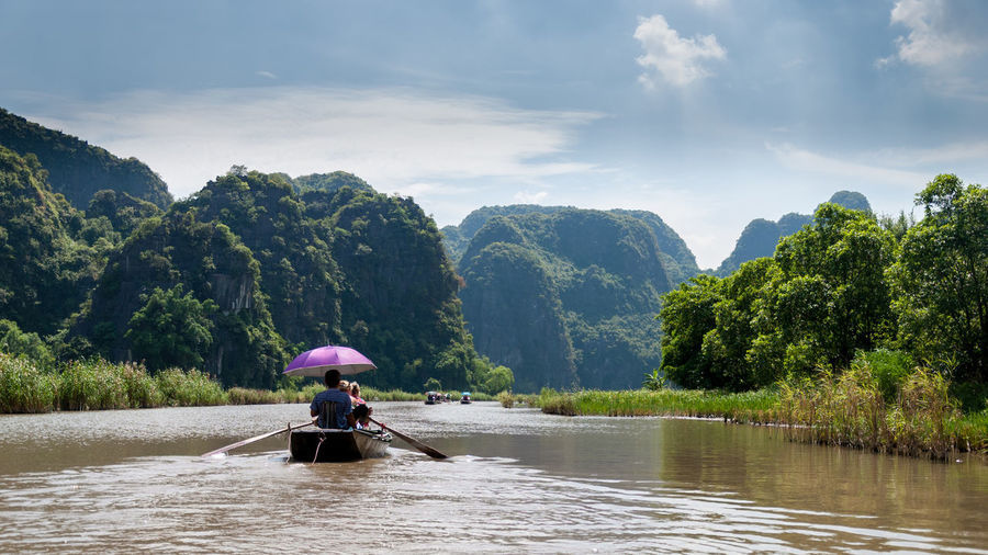 People Rowing Boat In River Against Sky