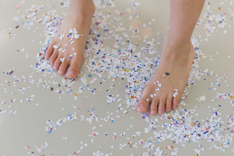Low Section Of Person Standing On Confetti