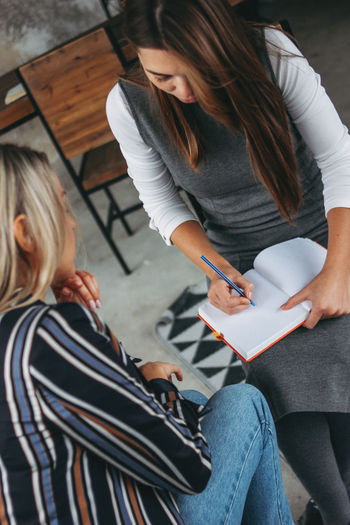 High angle view of woman sitting by colleague writing on book