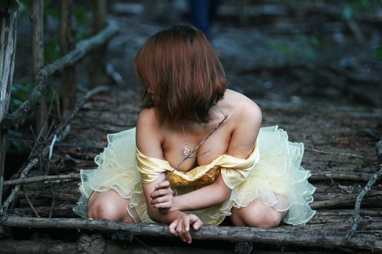 Sensuous woman kneeling on wooden structure