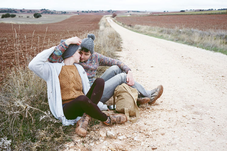 Couple Romancing While Sitting On Dirt Road During Winter