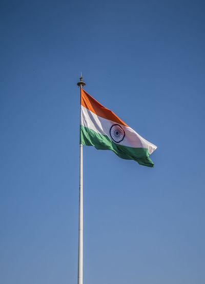 Low angle view of indian flag against clear blue sky