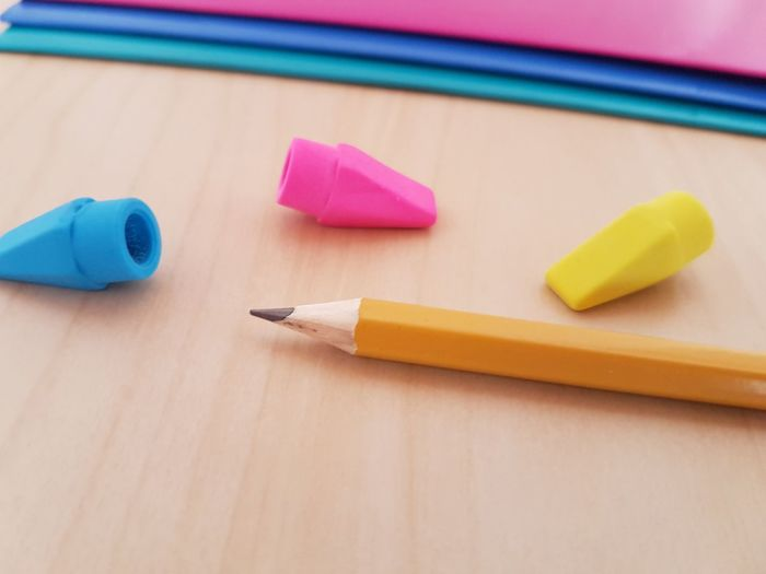 High angle view of pencil with colorful erasers on wooden table