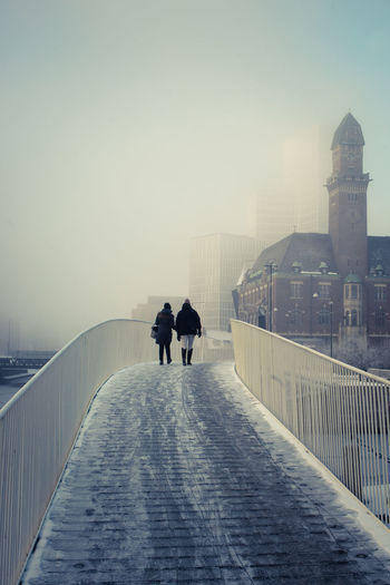 Rear view of people on footbridge against sky in city during winter
