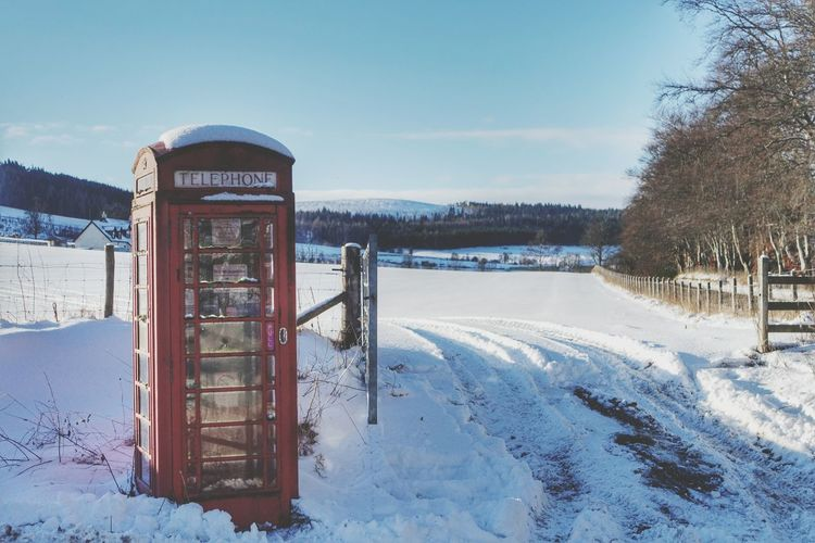 Telephone booth on snow covered landscape in winter