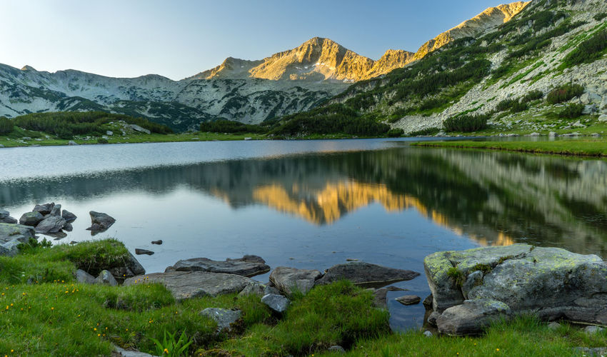 A gilded mountain peak reflects in the waters of a crystal clear lake Muratovo Lake Beauty In Nature Bulgaria Day Idyllic Lake Mountain Mountain Range Nature No People Outdoors Pirin Pirin Mountain Reflection Scenics Sky Tranquil Scene Tranquility Water
