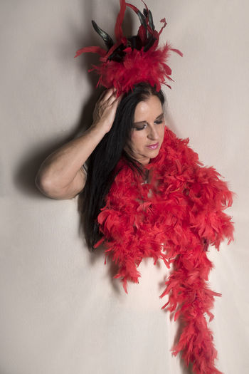 Woman wearing feather boa against white background