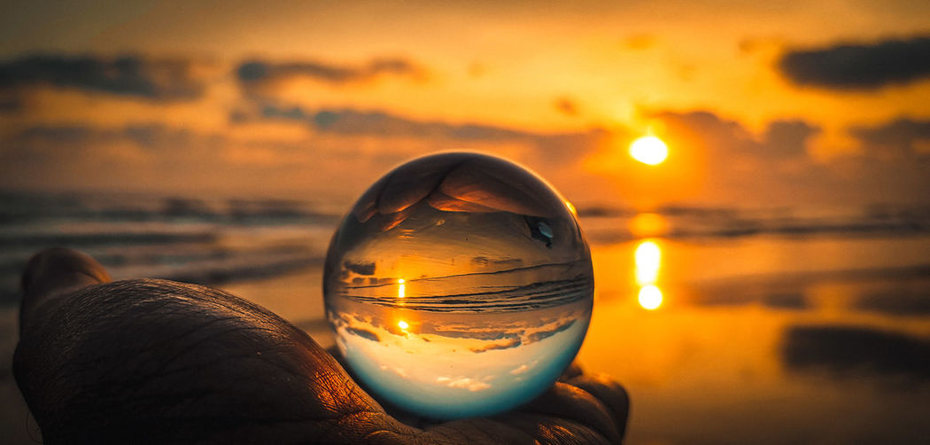 Close-up of person hand holding crystal ball against sea and sky during sunset