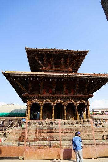 Rear view of man visiting temple against clear sky