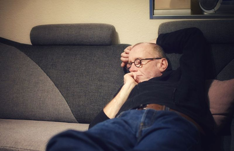 Man sleeping on sofa at home