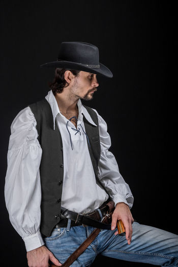 Handsome young man. This is an American cowboy. A vow to a white shirt, brown waistcoat and blue jeans. Black shoes on the feet. Carries a shtyapa, on a belt two pistols. The hair is of medium length; on the face is a beard and mustache. Authentic photo. Culture of America. Cowboy Wild West America American Gun National Authentic Moments Lifestyles Lifestyle One Person Candid Authentic Hat Clothing Three Quarter Length Black Background Adult Men Males  Portrait Waist Up Mature Adult Contemplation Confidence  Looking Away