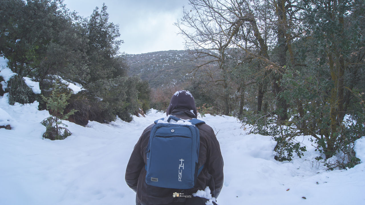 rear view, winter, real people, cold temperature, snow, walking, backpack, nature, hiking, beauty in nature, weather, one person, day, leisure activity, adventure, exploration, scenics, lifestyles, warm clothing, outdoors, standing, men, tree, sky, people