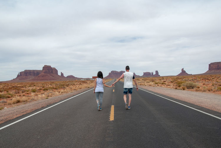 Togetherness Love Monument Valley Casual Clothing Cloud - Sky Couple - Relationship Direction Full Length Hand To Hand Lifestyles Ontheroad Outdoors Rear View Standing The Way Forward Togetherness Transportation Two People EyeEmNewHere Young Couple Road Marking Country Road Empty Road Moving Arid Landscape