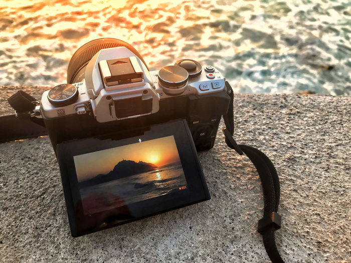 Close-up of camera on table at sunset