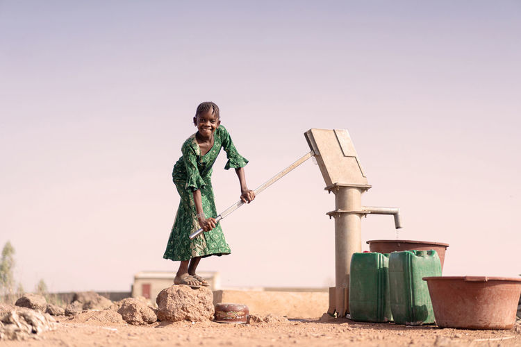Full length portrait of girl using water pump on land